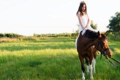 Charmig flicka i vitt klänningsammanträde på häst i fältet Royaltyfria Bilder