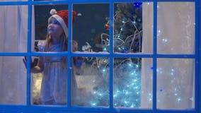 Charmig flicka till och med fönster i jultomtenhatt arkivfilmer