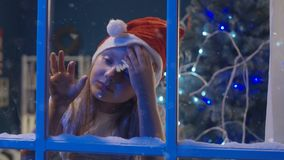 Charmig flicka till och med fönster i jultomtenhatt lager videofilmer