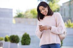 Charmig gladlynt flicka som kontrollerar hennes email arkivfoto