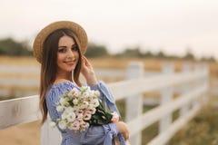 Charmig gravid kvinnah?ll en bukett av blommor Lyckligt kvinnaleende Framtida moder i natur arkivbild