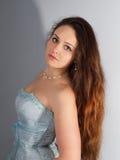 Charmig härlig ung kvinna i en blå klänning med långt tjockt D Arkivbild