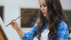 Charmig konstnärflicka som målar en bild på kanfas arkivfilmer