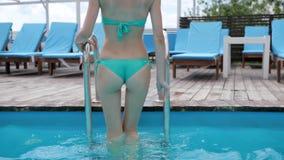 Charmig kvinna i bikiniklättring ut ur simbassäng på stege på blått vatten för bakgrund, sexig ung kvinna arkivfilmer