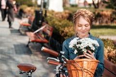 Charmig kvinna med den hållande buketten för cykel av blommor på bänk royaltyfri fotografi