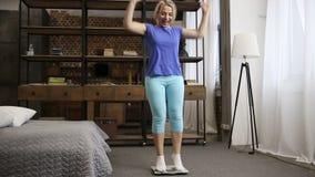 Charmig kvinna med skalan som firar viktförlust stock video