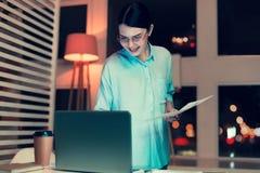 Charmig kvinna som kontrollerar information som påstås på utskrift Royaltyfri Foto