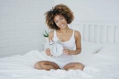 Charmig kvinna som poserar på säng med klockan Arkivfoton