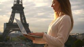 Charmig kvinna som pratar vid bärbara datorn nära Eiffeltorn i ultrarapid arkivfilmer