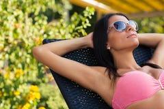 Charmig kvinna som solbadar på deckchairen Arkivbild