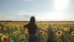 Charmig kvinna som tycker om fritid i solrosfält arkivfilmer
