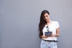 Charmig latinsk kvinna som rymmer hennes digitala minnestavladator, medan stå mot gataväggbakgrund med kopieringsutrymmeområde fö Royaltyfri Foto