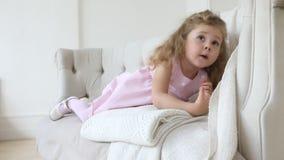 Charmig liten flicka som poserar på soffan arkivfilmer