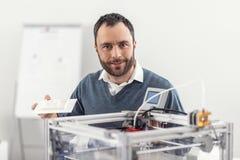 Charmig man som poserar med en modell nära skrivaren 3D Arkivbild