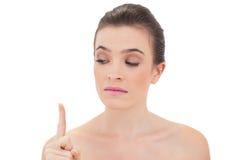 Charmig naturlig brun haired modell som ser hennes finger Fotografering för Bildbyråer