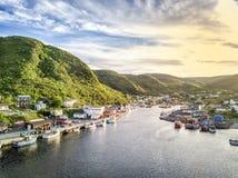 Charmig småaktig hamn med gröna kullar och träarkitektur, Royaltyfri Bild