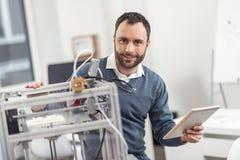 Charmig tekniker som kontrollerar skrivaren 3D till och med minnestavlan Royaltyfri Fotografi