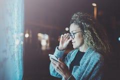 Charmig trendig kvinna med ögonexponeringsglas som ser på skärmsmartphonen på den ljusa asken för bakgrund i den atmosfäriska nat Royaltyfria Bilder