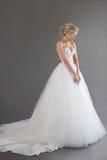 Charmig ung brud i lyxig bröllopsklänning nätt white för flicka Sinnesrörelser av lycka, grå bakgrund arkivfoto