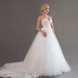 Charmig ung brud i lyxig bröllopsklänning nätt white för flicka Sinnesrörelser av lycka, grå bakgrund arkivbilder