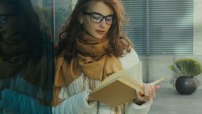 Charmig ung brunettstudent som läser en bok lager videofilmer