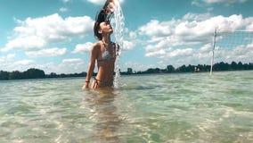 Charmig ung flicka i baddräkten som har gyckel i havet lager videofilmer