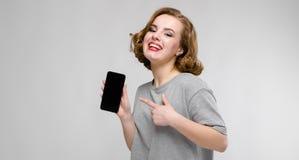 Charmig ung flicka i en grå T-tröja på en grå bakgrund En flicka rymmer en telefon i hennes hand Arkivbilder