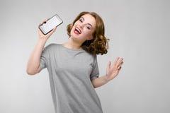 Charmig ung flicka i en grå T-tröja på en grå bakgrund En flicka rymmer en telefon i hennes hand Royaltyfria Bilder