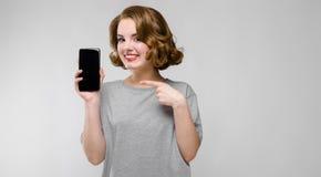 Charmig ung flicka i en grå T-tröja på en grå bakgrund En flicka rymmer en telefon i hennes hand Arkivfoton