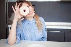 Charmig ung kvinna i köket Önskar att äta sötsaken glasade munken Att att göra roliga framsidor Fotografering för Bildbyråer