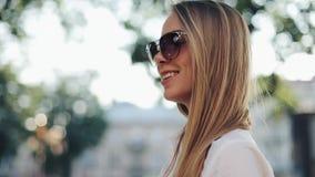 Charmig ung kvinna med ett storartat brunt hår och en stilfull solglasögon Den attraktiva unga damen rusar i staden stock video