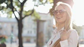 Charmig ung kvinna med ett storartat brunt hår och en stilfull solglasögon Den attraktiva unga damen rusar i staden lager videofilmer
