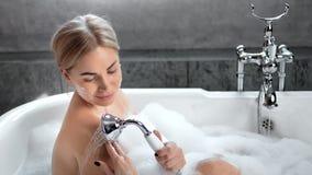 Charmig ung sexig kvinna som tar duschen som tycker om att bada som omges av skummedelskottet stock video