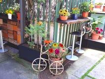 Charmig uteplats med blommor och tappningcirkuleringen Arkivfoto