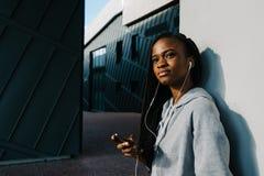 Charmig utomhus- stående av den mystiska unga afro--amerikan flickan i hörlurarna som lutar på väggen Royaltyfria Bilder