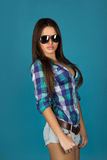 Charmig vuxen brunett i solglasögon på blå bakgrund Arkivbild
