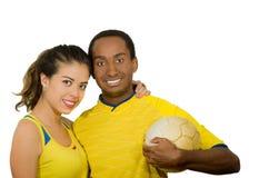 Charmiga mellan skilda raser par som bär gula fotbollskjortor som kramar vänskapsmatch, medan posera för kamerainnehavboll, vit Royaltyfri Fotografi