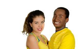 Charmiga mellan skilda raser par som bär gula fotbollskjortor som omfamnar vänskapsmatch, medan posera för kamera, vit studio Royaltyfri Foto