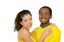 Charmiga mellan skilda raser par som bär gula fotbollskjortor som omfamnar vänskapsmatch, medan posera för kamera, vit studio Royaltyfri Bild