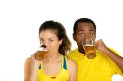 Charmiga mellan skilda raser par som bär gula fotbollskjortor som poserar för hållande ölexponeringsglas för kamera och ler, vit Arkivbilder