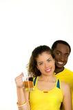 Charmiga mellan skilda raser par som bär gula fotbollskjortor som poserar för hållande ölexponeringsglas för kamera och ler, vit Royaltyfri Bild
