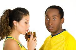 Charmiga mellan skilda raser par som bär gula fotbollskjortor som poserar för kamera, medan kvinnan dricker från ölexponeringsgla Royaltyfri Bild