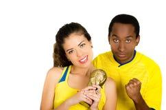 Charmiga mellan skilda raser par som bär gula fotbollskjortor som rymmer den lilla trofén som poserar för kameran, vit studio Fotografering för Bildbyråer