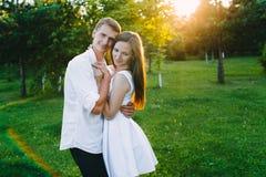 Charmiga par som kramar i en grön skog arkivbild