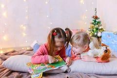 Charmiga små flickor spelar tillsammans och pratar och att ligga på golv och Royaltyfria Foton