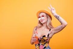 Charmigt för danandefred för ung kvinna tecken, medan ha en ny orange fruktsaft royaltyfri fotografi