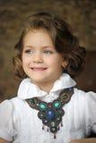 Charmigt flickabarn i en vit blus med en härlig halsband arkivbild