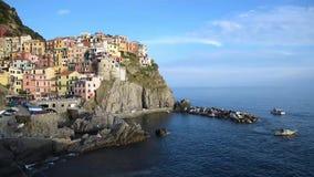 Charmigt härligt landskap med ett fartyg på havet och ljusa kulöra hus på vagga på sjösidan av Manarola i Cinque Terre, stock video