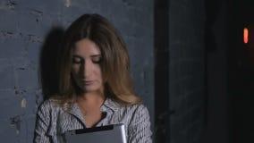 Charmigt kvinnaanseende nära det stenväggen och innehavet en minnestavla i händer stock video