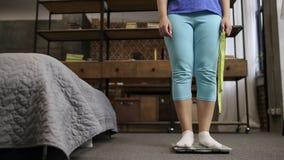 Charmigt kvinnaanseende på skalan som mäter vikt arkivfilmer